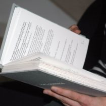 A close up of someone holding Topo Graphica, the book, open.